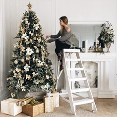 Woman putting up the final decorations on the Christmas tree in a cozy room. Photo by oh.anya on Twenty20