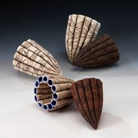"""Lisa Ellul, Artist, Pods, """"Seedpods were the inspiration for these pieces. Sage and lavender leaves have been rolled onto the surface of the clay leaving behind a skeletal imprint, almost like  the fossilized wing of a dragonfly.  The pods are constructed from white, red and black earthenware clay and fired to 1120 degrees Celcius."""" (narrative from website), 15cm"""