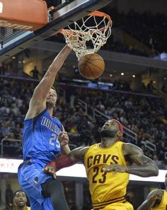 Oct 17, 2014; Cleveland, OH, USA; Dallas Mavericks forward Chandler Parsons (25) dunks against Cleveland Cavaliers forward LeBron James (23) in the first quarter at Quicken Loans Arena. Mandatory Credit: David Richard-USA TODAY Sports