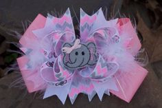 This hairclip is a beautiful stacked hairbow embellished with a feather and an elephant head feltie ...