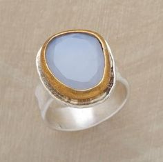 Like a window open to the sky, irregularly faceted blue chalcedony is framed in a brass bezel atop an oxidized sterling silver band. Exclusive. Whole sizes 5 to 9.