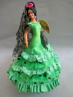 "Spanish Grain costume doll in Flamenco costume. She wears a sweeping green satin ""traje de flamenca"" (flamenco costume) with falbalas in cloth and tulle netting with a pattern of black dots, and short black lace shoulder sleeves. on her head, she wears a black mantilla with long black lace and a dark pink flower, and two smal pearls at her ears. She holds a fan with a design of bullfighting in her left hand. She is a typical model of the Spanish flamenco dolls of the Grain brand. She stands…"