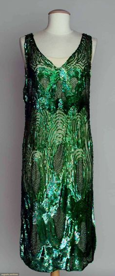 "EMERALD SEQUIN PARTY DRESS, 1920s All-over irridescent green sequins w/ bugle beaded ovals on net, B 38"", H 40"", L 44.5"", (some sequin & bead loss) very good."