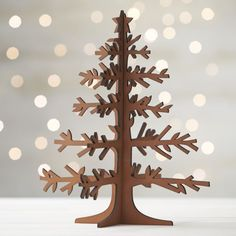 Graphic wood trees are laser-cut in realistic detail, easily assembled into dimensional, freestanding conversation pieces.  Large tree with star top and mid-tone finish can be paired with our laser-cut animals and village for a full decorative statement. Laser-cut plywoodMid-tone finishMade in China.