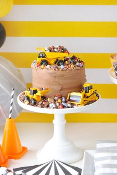 A chocolate birthday cake inspired by construction trucks. Decorated with rock candies and yellow toy trucks. Party Zone Party styling by Happy Wish Company. Photography by Tammy Hughes Photography. Stationery by Minted artist, Anne Holmquist.