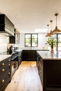 Natural wooden floors and brass accents bring a warmth to this stunning kitchen extension. The cabinetry is painted in an off-black colour called Downing Street by Mylands and the handles are made in Birmingham by a company called Armac Martin Open Plan Kitchen Living Room, Home Decor Kitchen, Home Kitchens, Kitchen Ideas, Kitchen Layout, Modern Kitchen Design, Interior Design Kitchen, Küchen Design, Home Design
