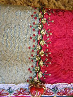 """I don't know if you can tell, but this seam started out with just gold rick-rack. I did herringbone in green, wove it in red, then added the the trios of stems on each side."" - Lin Moon Flickr"