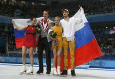 Second-placed Ksenia Stolbova (L) and Fedor Klimov (2nd L) of Russia pose with compatriots, first-placed Tatiana Volosozhar (2nd R) and Maxim Trankov, in front of the Russian national flag, after the figure skating pairs free skating at the Sochi 2014 Winter Olympics, February 12, 2014. REUTERS/Alexander Demianchuk