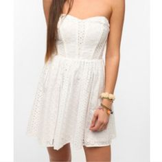 """Urban Outfitters White Eyelet Strapless Dress Urban Outfitters Breezy, woven cotton strapless dress from Kimchi Blue. Topped with allover dainty eyelet embroidery. Piping detail along the bodice. Smocked, elastic back for a sure fit. Full, gathered, A-line skirt. Hidden zip at the side. Fully lined.   Purchased for my daughter but didn't fit.   Measurements: 23.5"""" length 13.5"""" length from underarm  Content & Care: Cotton. Hand wash. Urban Outfitters Dresses Mini"""