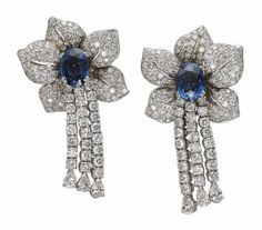 A SET OF SAPPHIRE AND DIAMOND JEWELLERY. The brooch designed as a cluster of pavé-set diamond leaves centering upon an oval-shaped sapphire and suspending three lines of brilliant-cut diamonds, each with a pear-shaped diamond terminal, a pair of ear pendants and a ring en suite, mounted in gold, brooch 6.9 cm, earrings 6.0 cm [Earrings only]