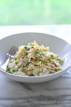 Tuna Pasta Salad with Dill & Peas yield: 4 SERVINGS prep time: 10 cook time: 15 total time: 25 INGREDIENTS: 1 lb. mini bowtie pasta 1 cup frozen peas 1/2 cup diced red or white onion 3/4 cup diced dill pickle 2-5 oz. cans tuna, drained {I used albacore tuna packed in water} 1/2 lemon, juiced 1 cup real mayonnaise 1 tablespoon dried dill salt & pepper, to taste