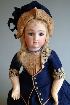 The lovely antique costume of navy blue silk with creamy lace and silk accents delights her. The luxurious matching bonnet enhances the appeal, along with antique leather shoes and under things. Her composition body is in lovely condition.