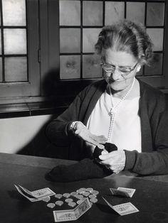 Oudere vrouw telt haar geld verstopt in een oude sok, briefjes van 2 1/2 gulden liggen op tafel, Nederland 1958.