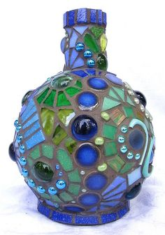 Poseidon Bottle Mosaic    Green and blue mosaic on a bottle substrate with charcoal grout.  The swirls are different on each side.  Photo belongs to: Frances Green