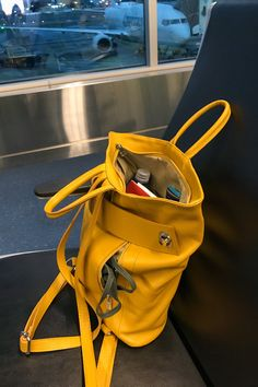Amazing travel tote backpack! Holds my book, 8oz water bottle, sunglass case, wallet & more - all my travel essentials. Love the small back zip pocket for my mask, passport & lip gloss. Not to mention this beautiful yellow mustard that goes with everything!! #carryonbag #carryontravel #fashionbags #ladiesfashion #passportholder #tote #leatherhandbags