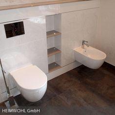Zwischen WC und Bidet aus dem Hause Keramag fand in einer Nische in der Vormauerung ein praktisches Regal mit Glaseinlegeböden seinen Platz