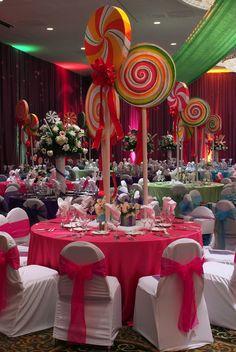 Temática de candyland con centros de mesa decorados con chupetes gigantes, precioso. #FiestaDeQuince