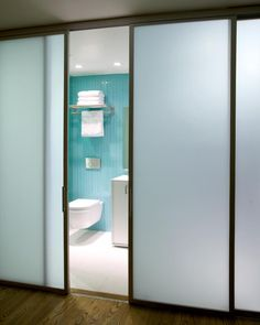 This Light And Bright Master Bathroom Features Bold Turquoise Tiles Paired  With A White Bathroom Floor. Frosted Glass Sliding Doors Are Used As  Dividers ...