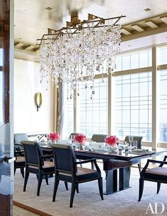 A handblown-glass-and-bronze chandelier designed by Randy Kemper and created by Megna Glass hangs above the light-filled dining room's 1960s French table | archdigest.com