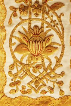 This detail shows gold work embroidery on a chasuble (Priest's vestment) from Clonard Monastery in Belfast. The chasuble is part of a set of festal vestments thought to have been made at the Good Shepherd Convent, Ormeau Road, Belfast, in the 1930s. The embroidery has been sewn by hand using a couching technique where the lines of metallic thread are applied to the surface fabric and secured by stitches from the reverse. Some motifs have been padded to create a raised effect for added emphasis.