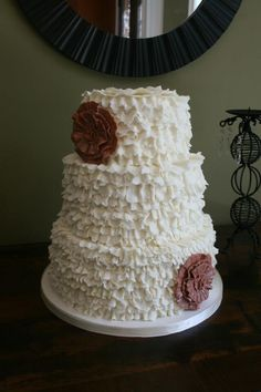 White ruffled 3 tiered wedding cake with brown fondant flowers-- try burlap & lace flowers or real flowers instead, but I like the ruffles