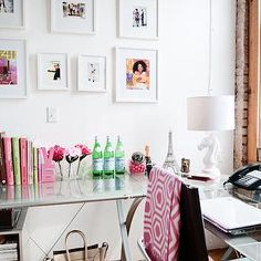 The Every Girl - dens/libraries/offices - exposed brick wall, brick wall, red brick wall, exposed brick, pink hex throw, pink and white hex throw, pink hexagon throw, glass desk, glass corner desk, glass and chrome corner desk, modern glass desk, L shaped glass desk, modern L shaped desk, leather desk chair, horse head lamp, horse chess piece lamp, white horse head lamp, pink love bookends, love bookends, gallery wall, framed photography, framed magazine cover, framed magazine pages, glass…