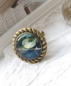 Gammeldags guld knop med fågel motiv i glas