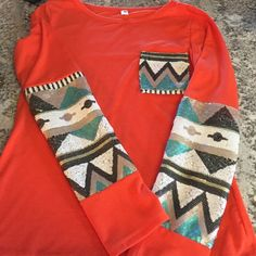 NWOTAztec Boutique Top w/ Ornate Sequin Detail Orange top with Aztec design in white, teal, black, and gold sequin detail on pocket and sleeves. BRAND NEW CONDITION! Boutique Tops