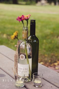 """Flowers in liquor bottles. Perfect for the reception at the bar. Maybe wrap in red or yellow lace to make it more """"superhero"""""""