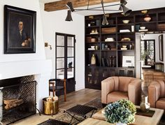 a pair of leather chairs next to a fireplace in a living room
