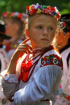 A young Romanian girl sporting a brightly hued traditional folk costume and garland-like headdress.