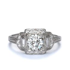 Spectacular Art Deco Diamond Engagement ring. A beautiful old European cut diamond weighing 1.02 cts and assessed in the setting by our graduate gemologist as L color and SI1 clarity is set within a low dome frame set with sixteen single cut diamonds and a pair of straight diamond baguettes (total weight 0.35 cts, HI color and VS-SI clarity). Embellished with a hand-engraved column motif down the shoulders, this vintage beauty is a size 7.5 and may be adjusted - please inquire. Platinum.