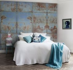 White bed with blue accents, distressed blue wall, serene bedroom