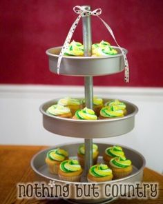 DIY dessert stand made from cake pans, threaded rod, metal tube conduit and drawer pull.  I would place the cake pans upside down to make cupcakes more accessible and decorate the lip of the pan with ribbon.