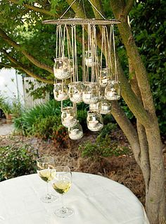 recycled glass jars made into a chandelier Looks like a round oven rack, chains & any kind or mix of bottles...