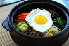Bibimbap is a large bowl of rice topped with an array of individually prepared vegetables and beef and served with seasoned red pepper paste (gochujang). Bibim means mixing, and bap means rice. The mixing usually happens at the table right before eating. Bibimbap served in a sizzling hot stone bowl is very popular at Korean restaurants and is my absolute favorite. The hot stone bowl gives the bottom layer of rice a nice golden crust, and the rest of the food sizzles while being mixed..