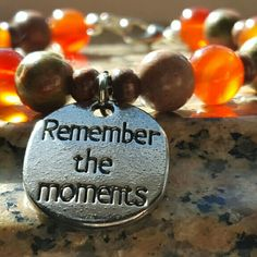 Semi-precious stone bracelet A beautiful combination of Unikite & Carnelian with wood accents.  Finishing touch of Remember The Moments silver charm.   Comes with a clasp. Jewelry Bracelets