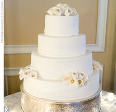 The couple's cake was a classic, four-tiered, white wedding cake with white sugar calla lilies clustered on the bottom and top tiers.