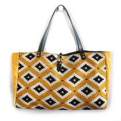 Bolso grande de tela de tapicería con estampado tribal en colores mostaza, negro y blanco. Laterales del bolso en tela de algodón en color mostaza.