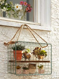 Bring an antique wire basket into bloom as a window box for potted succulents or other seasonal favorites with a length of rope, a scrap board, and a few nails. Thread the rope through the wire basket, knotting the ends around the wire, to fashion a loop for hanging. Drive two nails halfway into each short end of the scrap wood to create a shelf with pins for easy hanging.