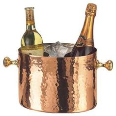 """The perfect accessory for your next soiree, this hammered copper ice bucket offers 2 sections for keeping your champagne and wine cool.    Product: Ice bucketConstruction Material: CopperColor: CopperFeatures: Tarnish-resistantDimensions: 7.5"""" H x 10.5"""" W x 7"""" D"""