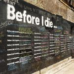 """Before I Die is an interactive public art project that invites people to share their hopes and dreams in public space. Painted with chalkboard paint and stenciled with the sentence """"Before I die I want to _______"""", the wall becomes an enlightening way to get to know your neighbors and discover what matters most to the people around you."""