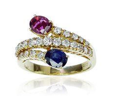 Ruby Sappire Diamonds Ring   Rubin & Saphir & Diamanten - kostbar komponierter Croisé-Ring      Anmutiger Goldring besetzt mit Rubin, Saphir und Diamanten.  Geschmeidig legt sich die Ringschiene um Ihren Finger.  Die Enden sind mit einem ovalen facettierten Rubin 0,663 ct. und einem dazu passenden ebenfalls facettierten Saphir 0,671 ct. besetzt.  Dazwischen funkeln 23 im leichten Verlauf gefasste Diamanten zusammen 0,569 ct.