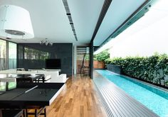 Formerly a semi-detached house, this site was converted to a bungalow. A lap pool is placed between the new house and the party wall, creating a private courtyard space. The 1st storey opens up to this space with the living, dining and dry kitchen adjacent. Upstairs, the master bathroom features a rainforest tree in the …
