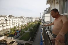 A resident stands on the balcony of his Parisian-style apartment. Construction first started in 2007 and although it is near completion and mostly open for business, local media regard Tianducheng as a ghost town, with only 2,000 homes occupied in the 10,000 home development (Reuters)