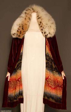 """VELVET & LAME OPERA COAT, MID 1920s Raspberry silk velvet, stuffed & oversize cat print fur collar, CF hem dips longer than in back, L 40"""", lined in red & blue ombre w/ gold brocade hydrangeas & leaves"""