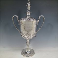 An Antique Victorian large Sterling Silver trophy cup and cover, having a round hand-chased body with fluted, floral, and anthemion leaf decoration, two cast side-handles with anthemion leaf thumb-pieces, an original cover with cast Milk-Maid finial, and sitting on a pedestal foot. Made by Horace Woodward & Co.Ltd, of London in 1899. The dimensions of this fine hand-made antique silver trophy cup & cover are height 51 cms (20 inches), spread across arms 30 cms (11.75 inches), and it weighs…