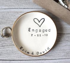 This personalized ring dish makes the perfect engagement gift!  The couple's two names and engagement date are stamped into this handmade ring holder.  Now the bride to be will have a safe place to set her gorgeous ring should she ever take it off. :)  Promise Pottery:  handcrafting ring dishes personalized your way, delivered on time.It's official.They're engaged.You need a gift.It's gotta be special.Classy and Unique.Like you.Well, you can relax.With me, you've got this:100% handmade,99.8% org Flat Engagement Rings, Engagement Gifts For Bride, Engagement Gift Boxes, Engagement Ring Holders, Ring Holder Wedding, Engagement Couple, Ring Dish, Wedding Rings For Women, Bride Gifts