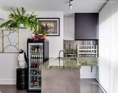 Varanda gourmet com churrasqueira integrada, bancada de mármore, quadros e uma geladeira para bebidas.