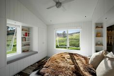 A spacious bedroom with white paneled walls and large windows. What do you think of the window seat and built-in storage?  Design by http://www.tgharchitects.com/